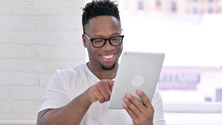 Portrait of Serious Casual African Man using Tablet