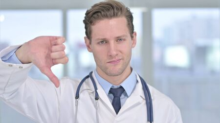 Portrait of Young Male Doctor showing Thumbs Down in Office