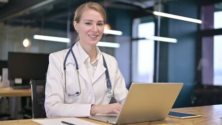 Cheerful Young Female Doctor Working on Laptop in Office