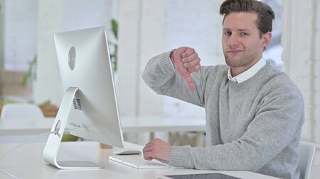 Young Man working on Desktop and doing Thumbs Down