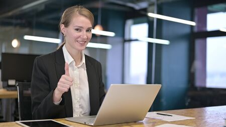 Young Businesswoman doing Thumbs Up in Office Stock fotó