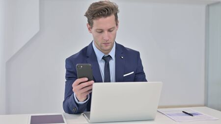 Young Businessman Working on Laptop and using Smartphone Stock fotó