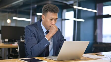 Sick Young Businessman Working on Laptop and Coughing