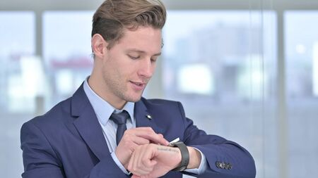 Portrait of Young Businessman using Smartwatch