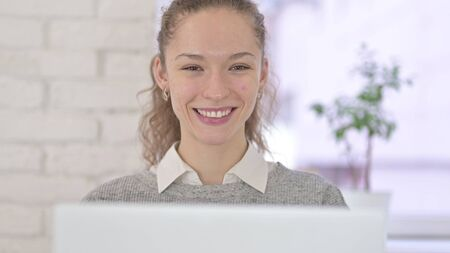 Young Latin Woman Working on Laptop and Smiling at Camera