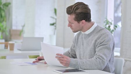 Creative Young Man checking Financial Documents, Reading