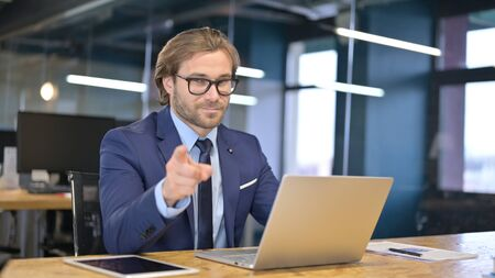 Cheerful Businessman Pointing finger and Inviting Stock fotó