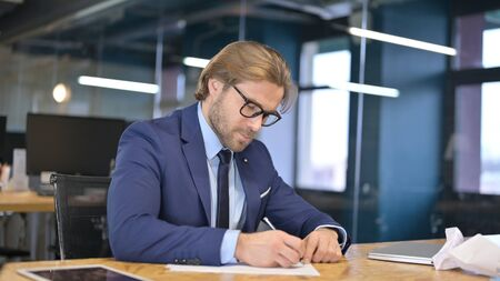 Angry Businessman Writing Documents on Office Desk Stock fotó