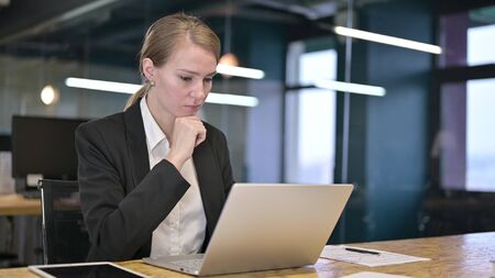 Young Businesswoman Thinking and Working on Laptop in Office