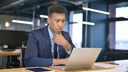 Young Businessman Thinking and Working on Laptop