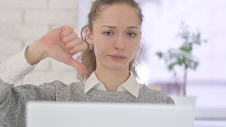 Thumbs Down by Young Latin Woman working on Laptop