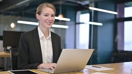 Young Businesswoman Working on Laptop and Smiling at Camera
