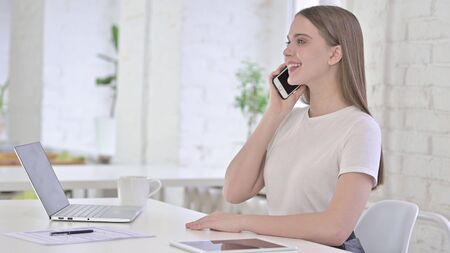 Happy Young Woman Talking on Smart Phone in Office Stock fotó