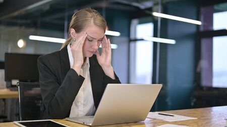 Tired Young Businesswoman having Headache in Office