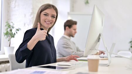 Ambitious Creative Woman showing Thumbs Up in Office
