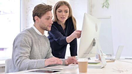 Creative People Discussing Work on Desktop in Office