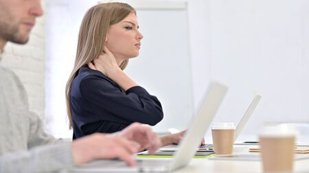 Creative Woman working on Laptop and having Neck Pain in Office Stock fotó