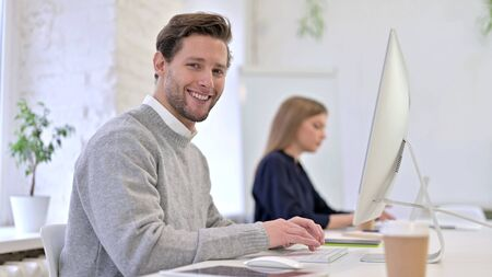 Young Man working on Desktop and Smiling at the Camera