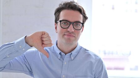 Portrait of Disappointed Young Man showing Thumbs Down