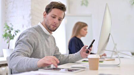 Ambitious Man Working on Smartphone, Tablet and Desktop Stock fotó