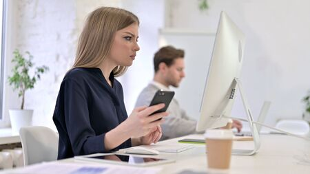 Creative Woman using Smartphone and Working on Desktop