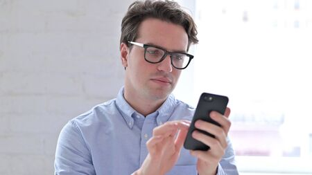 Portrait of Relaxed Young Man using Smartphone Stock fotó