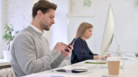 Serious Creative Professional Using Smartphone in Office Stock fotó