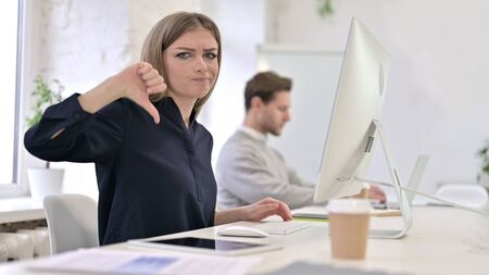 Disappointed Creative Woman showing Thumbs Down in Office