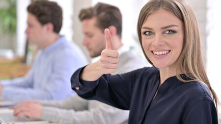 Portrait of Ambitious Creative Woman showing Thumbs Up in Office