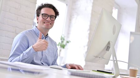 Ambitious Working Young Man doing Thumbs Up in Office