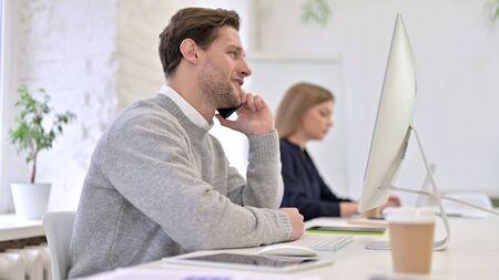 Happy Man Talking on Smart Phone in Office