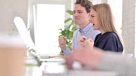 Creative Team Celebrating Success on Desktop by High-Five in Office