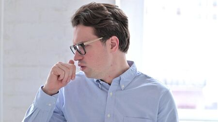 Portrait of Sick Young Man Coughing in Office Stock fotó
