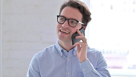 Portrait of Cheerful Young Man Talking on Smartphone