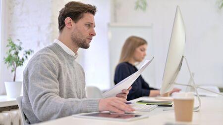 Serious Man Reading Documents and using Desktop Stock fotó