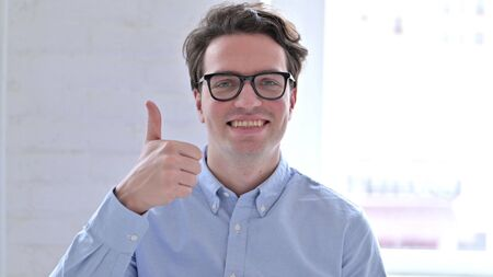 Portrait of Cheerful Young Man showing Thumbs Up