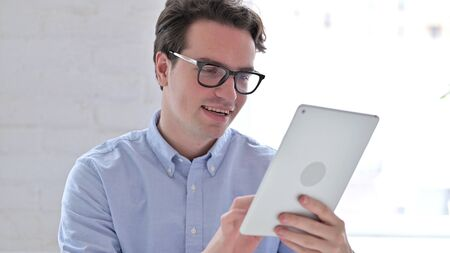 Portrait of Cheerful Young Man using Tablet