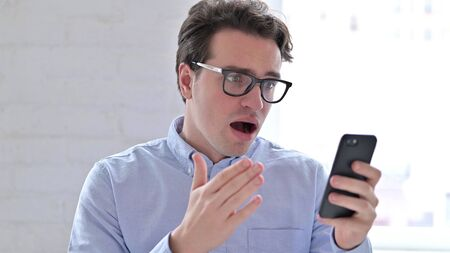 Portrait of Young Man reacting to Failure on Smartphone Stock fotó
