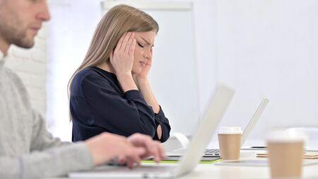 Tired Creative Female Professional having Headache in Office