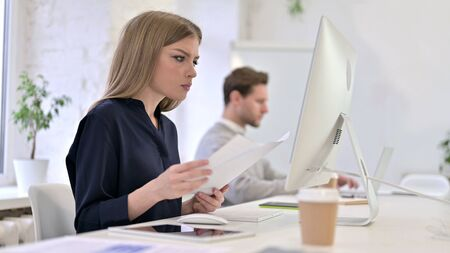 Creative Woman Reading Documents and Working on Desktop