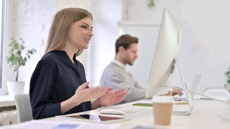 Beautiful Creative Woman doing Video Chat on Desktop in Office
