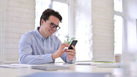 Cheerful Working Young Man using Smartphone in Office