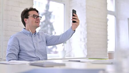 Cheerful Working Young Man doing Video Chat on Smartphone