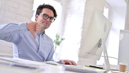 Disappointed Working Young Man showing Thumbs Down in Office