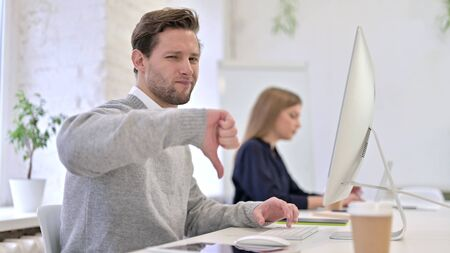 Upset Man showing Thumbs Down in Office