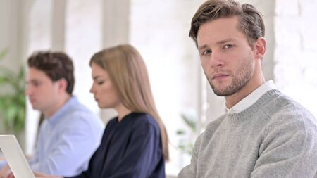 Portrait of Serious Man Looking at the Camera in Office