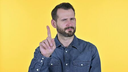 Portrait of Young Man saying No by Finger, Yellow Background