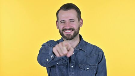 Portrait of Young Man Pointing Finger at the Camera, Yellow Background Stock Photo