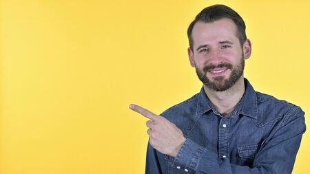 Portrait of Young Man Pointing at Product, Yellow Background