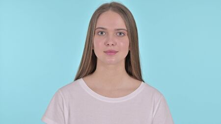 Beautiful Young Woman Looking at the Camera, Blue Background